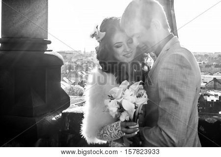 Bride with lily bouquet smiles while being huged by fiance on the rooftop of Gothic cathedral