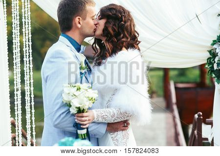 Bride and fiance kissing in the front of wedding altar
