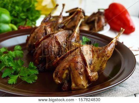 Roasted quail on a spit. Serving on a ceramic plate with greens. Close-up. Holiday menu.