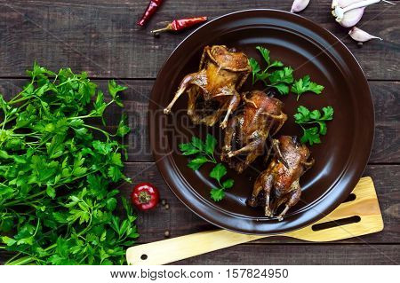 Roasted quail on a spit. Serving on a ceramic plate with greens. The top view. Holiday menu.