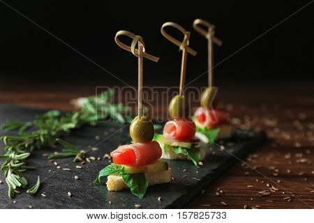 Gourmet canapes with herbs on slate plate