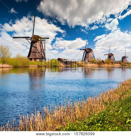 Sunny spring scene in the canal in Netherlands. Dutch windmills at Kinderdijk an UNESCO world heritage site. Morning in Holland.