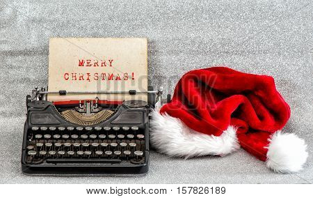 Old typewriter with red hat and sample text Merry Christmas. Retro style picture