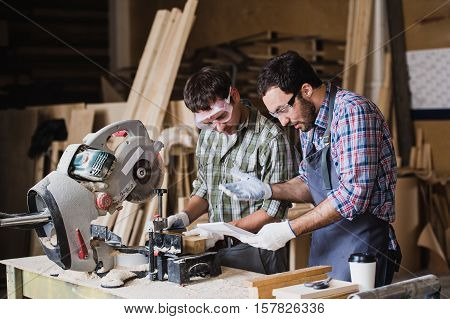 Inspector and carpenter discuss the process of making wood products for furniture.
