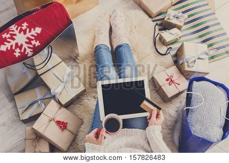Christmas online shopping top view. Female buyer click at screen of tablet, make internet order with credit card. Woman buy presents for xmas, among gift boxes and packages. Winter holidays sales