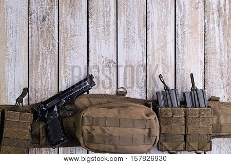 Military battle belt with ammo and gun on wooden table.Top view