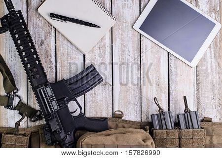 Riflenotebook with penPC tablet touch computerbattle balt with ammo on wooden table.Top view