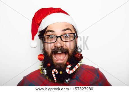 Sale, christmas, x-mas concept. Smiling and surprised young bearded man wearing a santa helper hat shocked over white background.