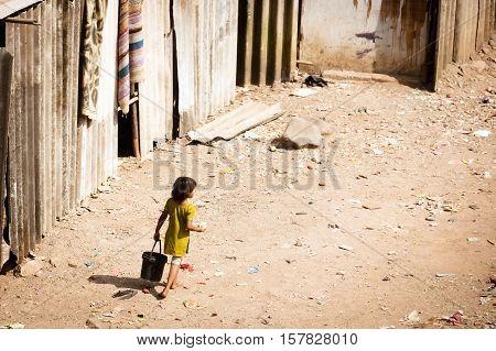 A child plays in piles of trash in a slum in Airoli, Mumbai, INdia