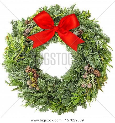 Christmas wreath from fir pine and spruce twigs with cones and red ribbon bow isolated on white background