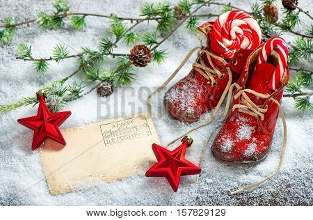 Christmas decoration red stars sweets and antique baby shoes on snow background. Empty postcard for your text