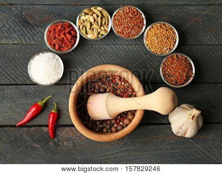 Composition with different spices and mortar on dark wooden background