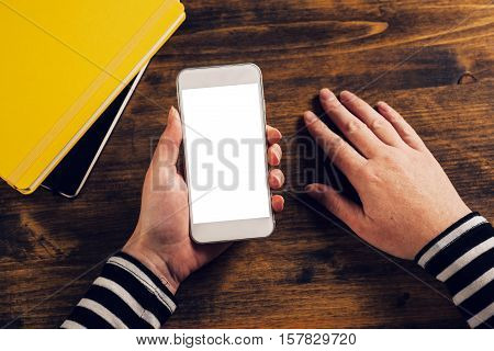 Top view of female hands holding mobile smarthone with blank screen as copy space above office desktop