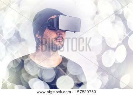 Male actor immersed in experience of virtual reality environment wearing vr goggles augmented-reality headset and enjoying 3d cyberspace multimedia content.