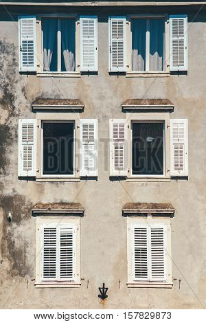Weathered building facade and old windows with classic wooden venetian shutters blinds mediterranean europe architecture vintage style