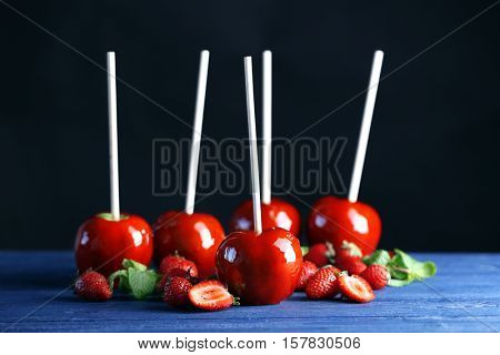 Candy apples with strawberry on dark background