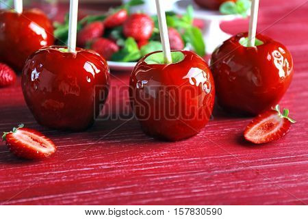 Candy apples with strawberry on red wooden background