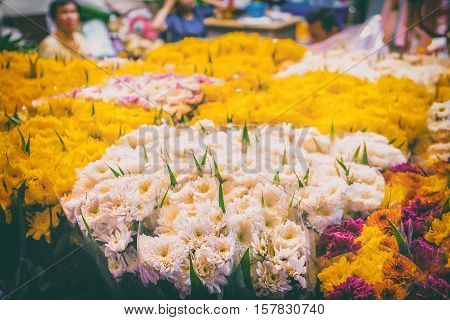 Flowers for sale at the night flower market in Bangkok Thailand. Vintage style soft focus.