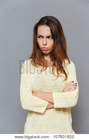 Portrait of angry upset woman standing with arms crossed and looking away isolated on the gray background