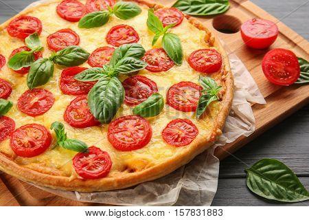 Fresh tasty pizza Margarita on wooden tray, closeup