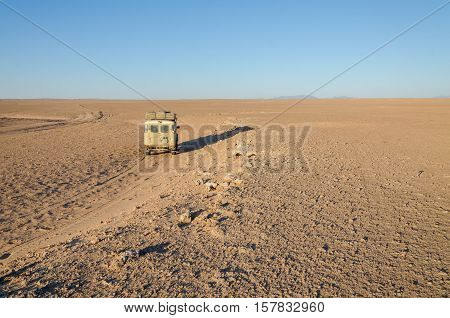 Vintage 4x4 offroad vehicle driving in empty flat and rocky Namib Desert of Angola.