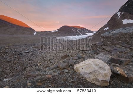 Vibrant red colored mountains by sunset in a glacier valley