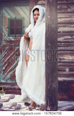 Young woman in white lingerie with white long coat under the umbrella of a log cabin in winter