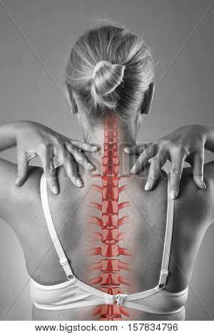 Spine pain woman with backache and ache in the neck black and white photo with red backbone on gray background