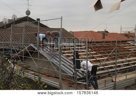 VAPRIO ITALY - NOVEMBER 7 2016: men at work on a roof of ancient rural building