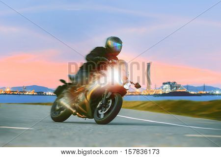 young man riding sport touring motorcycle on asphalt highways against beautiful lighting of urban industry scene use as modern people lifestyle and holiday activities