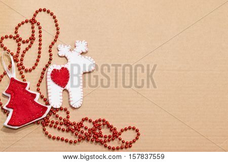 Handmade Christmas toys. Step-by-step. Red and white reindeer Christmas tree red beads. Children holiday crafts. Top view. Background - Cardboard