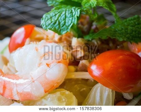 Close-up of shrimp and pomelo salad. Shallow depth of field with one shrimp pieces of pomelo and a cherry tomato in focus.