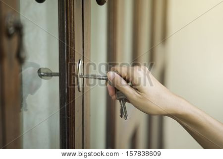 female hand putting house key into front door lock of house