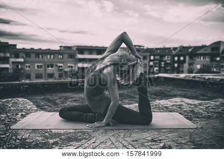 Beautiful woman practicing yoga on the roof,Eka pada Rajakapotasana/Pigeon pose