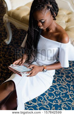 incredible beautiful black girl sitting on the floor chatting with friends in internet. Luxury interior with blue floor and classic furniture.