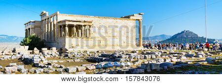 Athens, Greece - October 14, 2016: Tourists near Erechtheum temple ruins decorated with Caryatids female statues in Acropolis