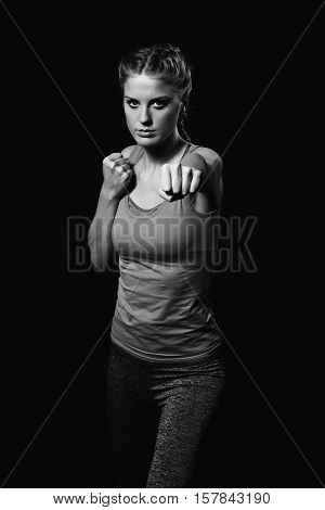 Black and white photo of beautiful young woman is exercising.