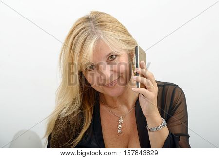 beautiful mature blond woman talking on mobile phone