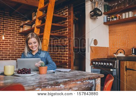 Attractive young blonde woman sitting at a table in her modern loft apartment using a digital tablet