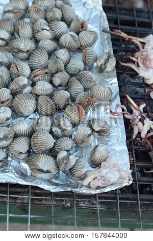 Grilled cockles placed on foil on the stove