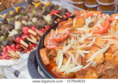 Street food - The pices of beef with onion and tomatoes prepared in bowl on farmers market