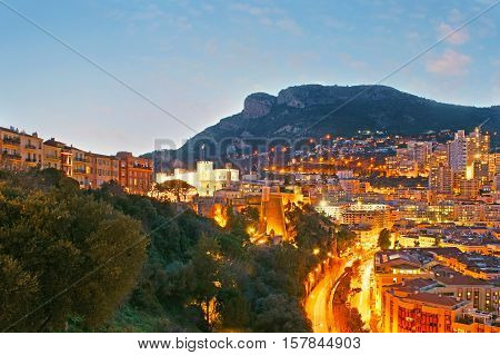 The lights of Monaco with the brightly illuminated Prince's Palace in Monaco-Ville and residential quarters of La Condamine at the mountain foot and othe slope.