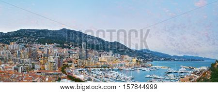 Panorama of Monaco coastline in the evening the Port Hercules surrounded by densely built-up wards of La Condamine and Monte Carlo on the background.
