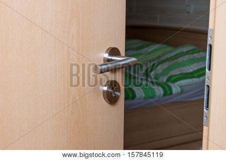 Half-open door to the bedroom. Focus on the door handle