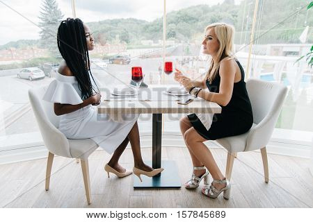 two sexy woman drinking wine in a restaurant in front of the big windows. European and african woman are chatting and have fun. African girl is in white, blonde girl is in black dress. Luxury interior