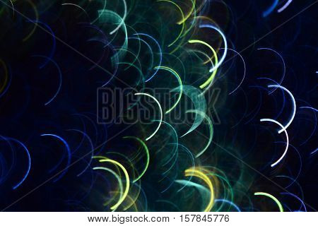 Abstract photo by blue and green semicircular light lines to background.