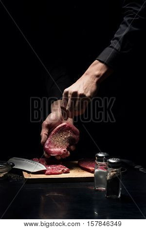 Flavored and tasty. Close up of young male chefs hands spicing the meat while working in restaurant and cooking.