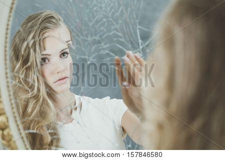 Beautiful sad woman reflection in broken mirror