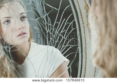 Teenager after nervous breakdown watching herself in broken mirror