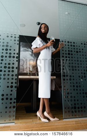 Young beautiful african woman staying in hotel room with modern design. She is wearing midi white dress with bare shoulders and has a glass of red wine in her hand.